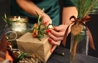Pakowanie świątecznych prezentów. Kobieta pakuje prezent świąteczny