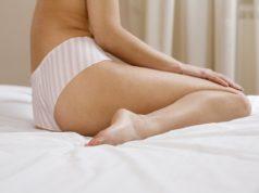 kobieta w figach siedząca na łóżku