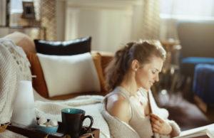 kobieta czytająca książkę w przytulnym domu
