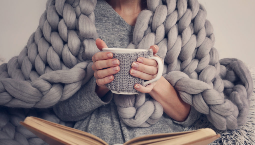 kobieta otulona kocem czytająca książkę