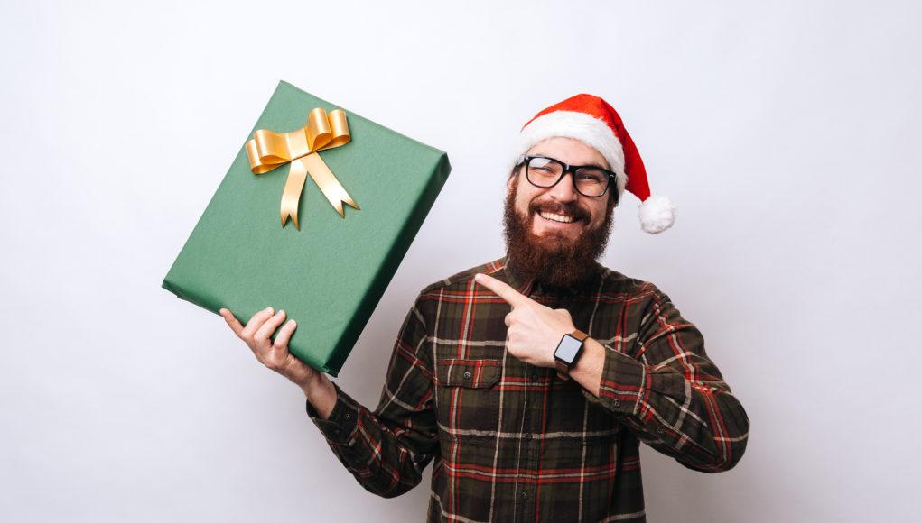 mężczyzna z brodą w czapce mikołaja i prezentem w dłoni