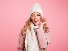 młoda dziewczyna w zimowym stroju na różowym tle