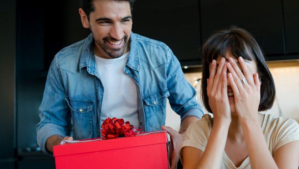 mężczyzna wręczający prezent ukochanej