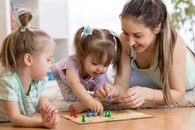 matka grająca z dziećmi w chińczyka