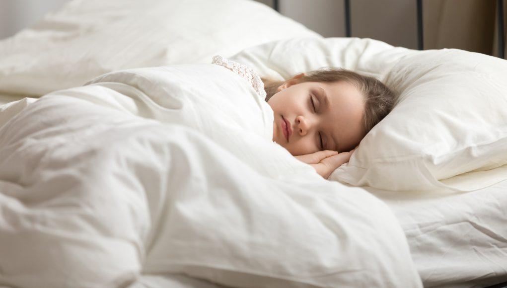 dziewczynka śpiąca w puchowej pościeli