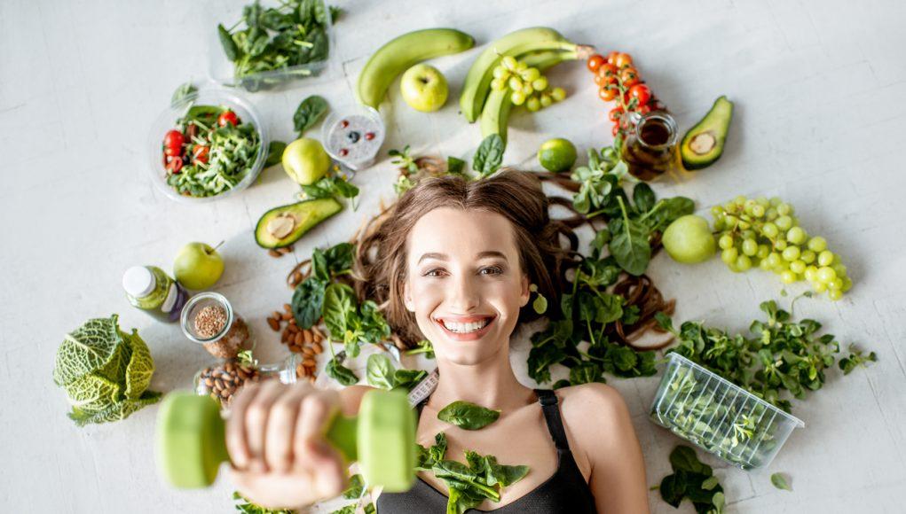 kobieta z ciężarkami warzywami owocami