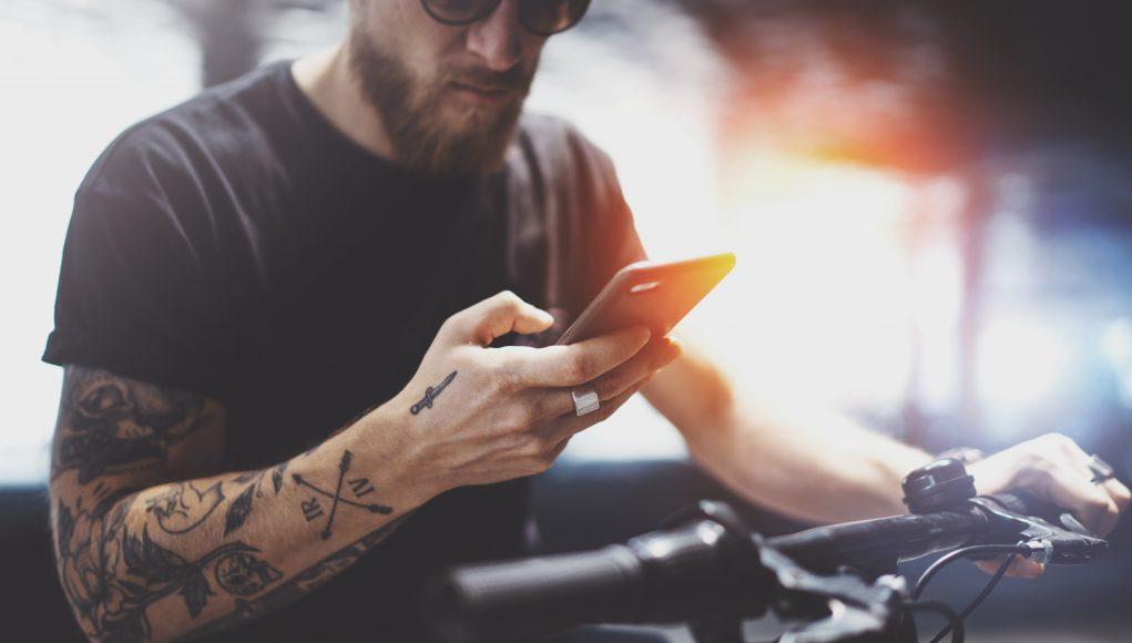 wytatuowany mężczyzna ze smartfonem w dłoni