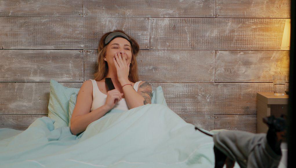 kobieta oglądająca w łóżku telewizję