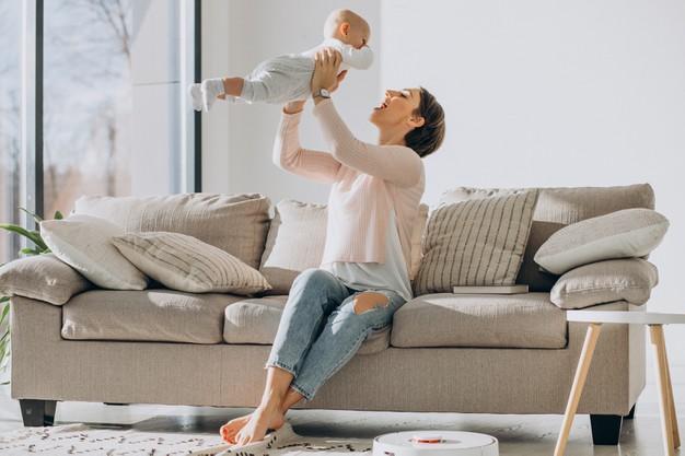 matka z dzieckiem i sprzątający odkurzacz automatyczny