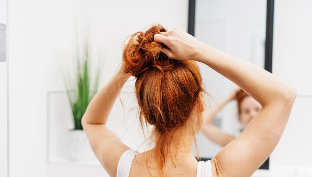 młoda ruda kobieta przed lustrem